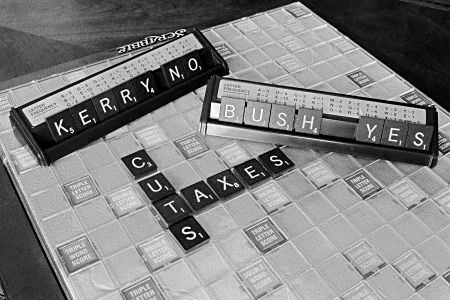 Scrabble board with Cut Taxes alread played with two players' racks on the board showing 'Bush Yes' and 'Kerry No' in the players' hands.